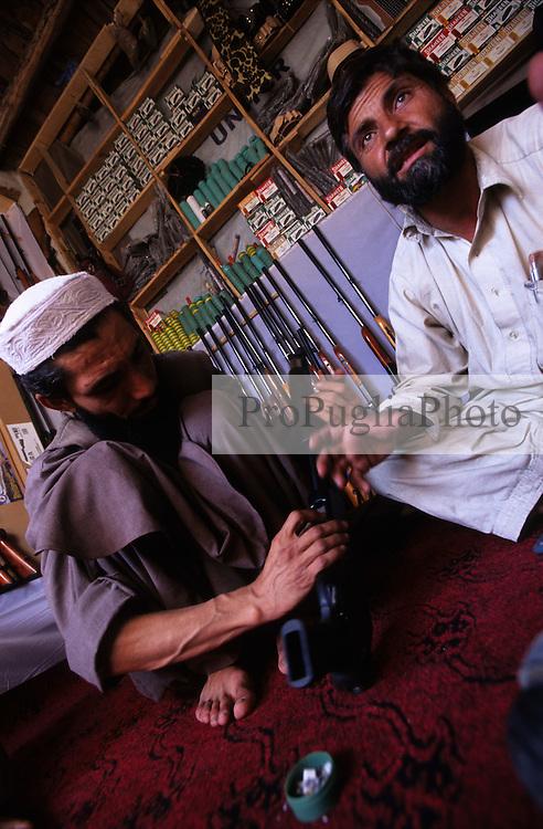 Kabul, 14 August 2005...A local shopkeeper sells Pakistani shotguns and ammunition...