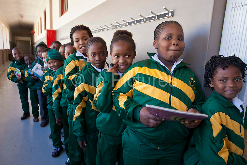 Young African school children line up in a queue waiting to go into their classroom in the corridor of Observatory Primary School, Cape Town, South Africa.  They are waiting for a literacy class and some of the children are holding their reading books.  The literacy class is supported by the Shine Centre which is a charity that aims to address the high illiteracy rate in South Africa by improving literacy levels among children in schools and disadvantaged communities.