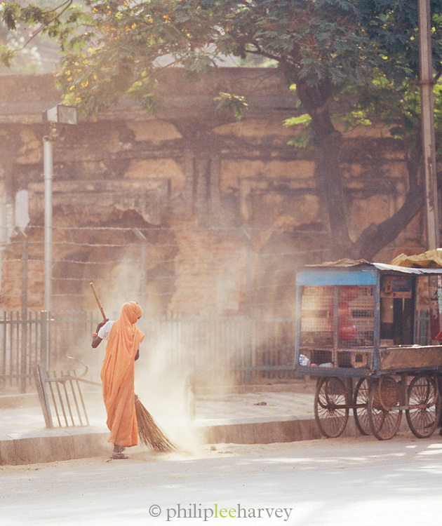 Young woman sweeping the streets with broom, Lucknow, Uttar Pradesh, India