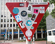 Various youth culture stickers on street sign Rotterdam, Netherlands