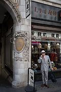 A foreign-looking gentleman stands talking into his phones hands-free outside Laird Hatters, on 5th July 2017, on the Strand in central London, England.