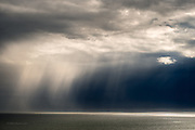 Short sunbursts during extensive periods of rain and dark skies over the Irish Sea seen from Holy Island. Even the brightest patches were heavy rain.