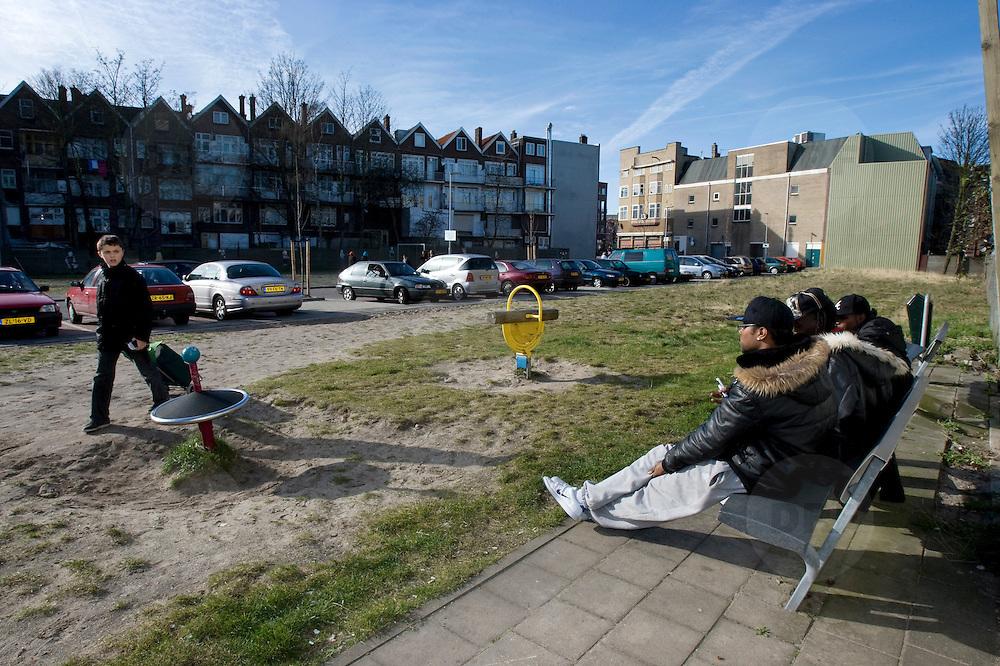 Nederland Rotterdam 14 maart 2008 20080314 .Stadsgezicht achterstandswijk Hillesluis Rotterdam Zuid, allochtone jongeren zitten op bankje in zonnetje bij braakliggend terrein dat tijdelijk als speelplaats is ingericht tot bestemming van de locatie duidelijk is..Foto David Rozing