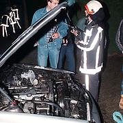 Brandbomaanslag op de auto van Willibrord Frequin aan de Koggewagen 14 Blaricum, politieagent Frank Kok overlegt met de brandweer
