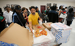 Angel Poventud, who voted early, volunteers his time to hand out pizza and snacks to people waiting in line. The wait time to vote at the Pittman Park precinct in Atlanta was reported to be three hours. Pizza and snacks were donated for the people waiting in line. Photo by Bob Andres/Atlanta Journal-Constitution/TNS/ABACAPRESS.COM
