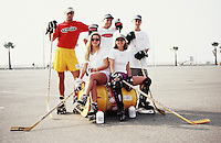 1998:  Ball hockey players sit on a yellow trash can sitting on its side before playing roller hockey on the weekends at the beach parking lot in Santa Monica, CA.  Men and women.  Southern California summer sport. Transparency slide scan. Sharon Rizzi.