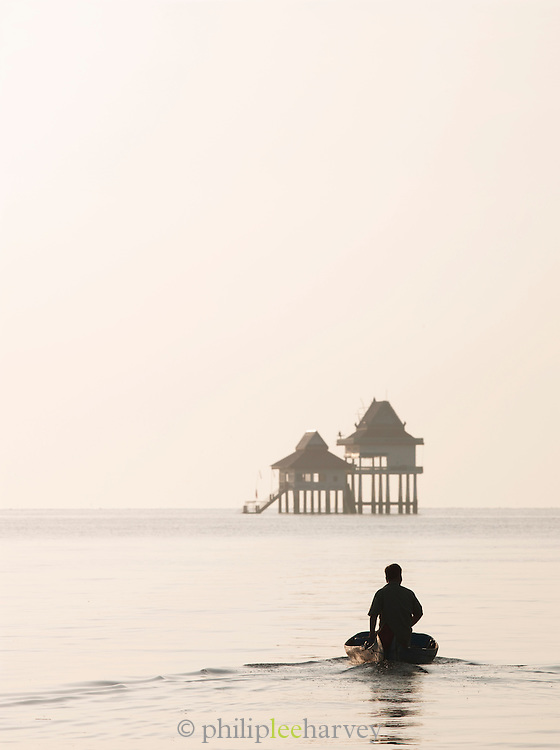 A small boat travels towards a Buddhist temple built isolated on the great Tonlé Sap lake, Cambodia