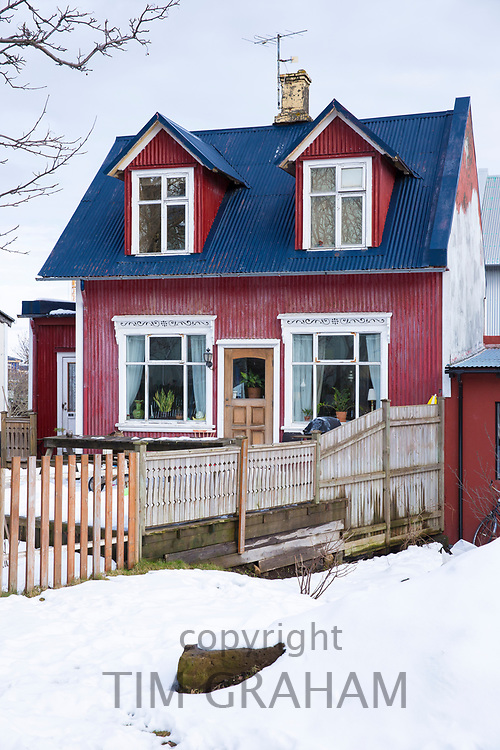 Traditional typical painted corrugated metal house, snow on the ground, in the old town area of capital city Reykjavik, Iceland