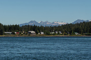 The tiny hamlet of Kupreanof across the Wrangell Narrows from Petersburg with the Alaska Coast Range of mountains behind in southeast Alaska.