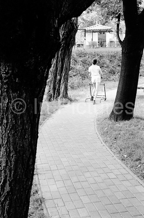 A boy walks through the tree lined avenue at the Institute. The Peto Institute, Budapest, Hungary