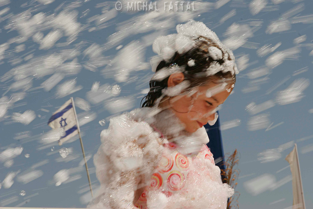 A refugee girl from one the northern cities of Israel at the refugee tent camp in the southern beach of Nitzanim enjoyes a foam game a on Friday, August 11, 2006. The camp was established as a private initiative, sponsered by the buisnessman Arkadi Gaidamac in order to absorb citizens from the northern cities of Israel that are threatened by Hezbollah attacks. Photo by Michal Fattal/ Flash90.