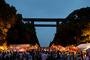 People, many in summer kimonos called Yukata enjoy festival stalls selling food drink and entertainment during the Mitama matsuri or festival of remembrance at the controversial Yasukuni Shrine in Chiyoda, Tokyo, Japan. Tuesday, July 13th 2010