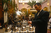 A waiter pours hot water from a silver urn for tea during an afternoon tea dance at the Waldorf Hotels Palm Court, Waldorf Hilton Hotel, Aldwych., on 16th March 1997, in London, England.
