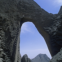 While Mark Newcomb (MR) waits above, Sam Lightner rappels off huge Shipton's Arch in the Kara Tagh Mountains near Kashgar and the Taklimakan Desert. (The figures are almost too small too see.)