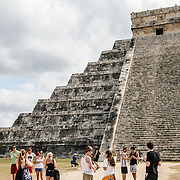 A group of tourists stand in front of the steps of the Temple of Kukulkan (El Castillo) at Chichen Itza Archeological Zone, ruins of a major Maya civilization city in the heart of Mexico's Yucatan Peninsula.