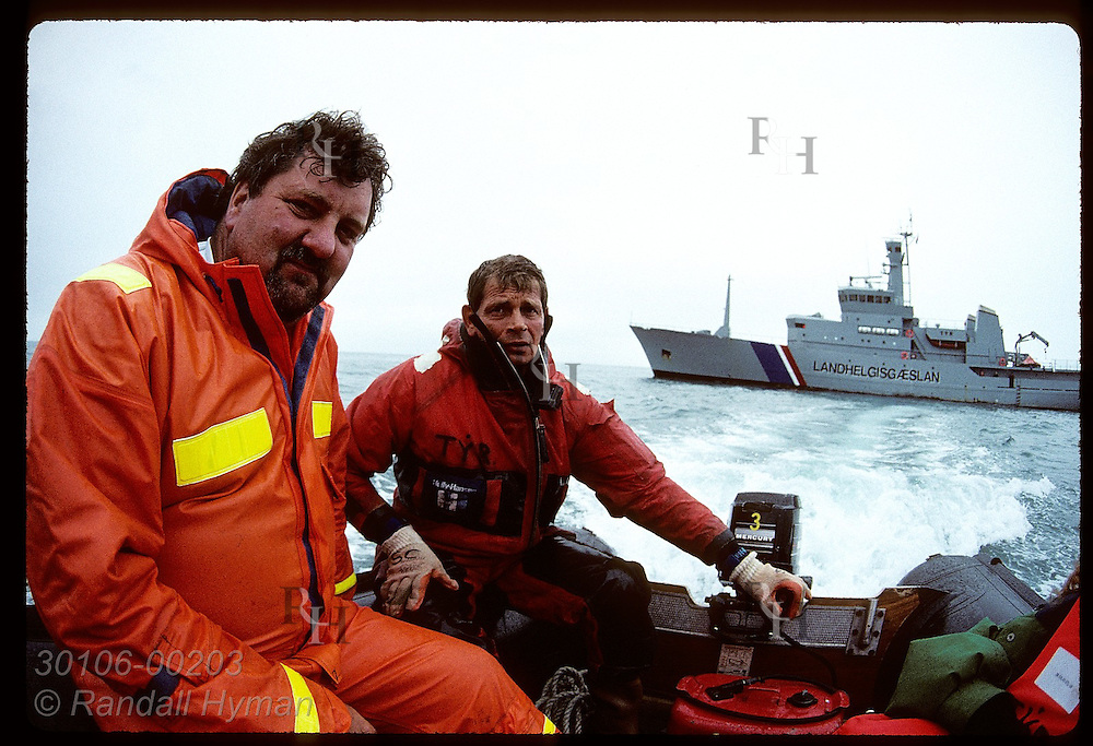 Two sailors ride in dinghy from coast guard ship Tyr (background) to go inspect a fishing boat. Iceland