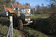 Tractor driving through gate, Suffolk farming landscape scenery, East Anglia, England