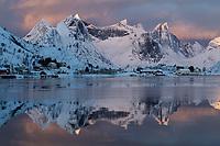 Low January sun illuminates distant mountain peaks across Reinefjord, Reine, Moskenesøy, Lofoten Islands, Norway