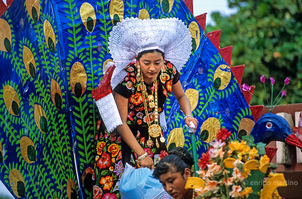 Juchitàn, Velas (traditional celebration), a procession with many carriages. The tehuanas of the Isthmus of Tehuantepec are the archetype of an ancient and legendary Mexico, told in the murales of Diego Rivera and impersonated also by Frida Kalho that often wore these traditional dresses. But these showy dresses, and the rich golden ornaments that accompany them, are above all an instrument of auto-representation for these active women which the control of the local markets confers an independent economic power that is reflected in the self confidence. Even in the development of the festivities, where the women often dance a lot among them while the men remain seated watching.