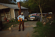 """BESSEMER, AL – OCTOBER 8, 2011: Blues legend Henry """"Gip"""" Gipson, 90, strums an acoustic guitar in front of his home before a performance in his backyard juke joint.<br /> <br /> After an altercation with the KKK in the 60's rendered his left hand badly broken, Gipson's method of guitar playing had to change. """"I had to crowd the strings,"""" Gipson said, describing the method that he adopted. Today, Gipson operates Gip's Place, one of few true remaining juke joints in the country. """"Music don't care no color,"""" Gipson said. """"And that's why I love blues, because blues deals with a story to tell you."""""""
