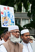 East End, London July 5th 2014. Rally and march against proposed cuts to National Health Service doctors' surgeries , specifically MPIG (Minimum Practice Income Guarantee payments) brought in to ensure practices in deprived areas had enough money to deliver high quality General Practice services. A group of Muslim men from the Bangladeshi community with placards listen to speeches.