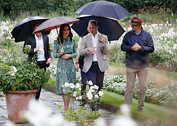 The Duke and Duchess of Cambridge and Prince Harry (partially obscured at left) visit the White Garden in Kensington Palace, London, as they meet with representatives from charities supported by Diana, the Princess of Wales.
