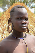 Mursi Tribe in The Omom River Valley, Ethiopia. A young tribeswoman with elongated earlobes, The Mursi tribe is a nomadic cattle herder ethnic group located in Southern Ethiopia, close to the Sudanese border.