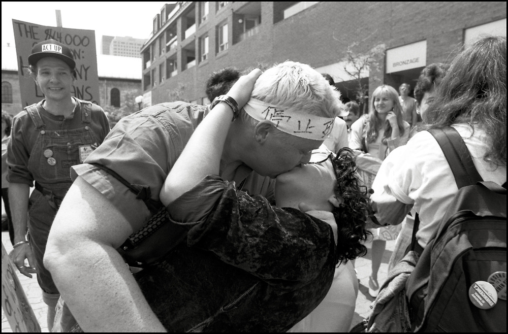 Gerri Wells and Garance Franke-Ruta participate in a kiss-in outside the Fifth International Conference on AIDS in Montreal, Canada, while Rollerena looks on.<br /> <br /> AIDS Activists from ACT UP NY en route to Montreal where they stormed the Fifth International AIDS Conference in Montreal, at the time a members-only event for doctors and HIV/AIDS researchers. They took over seats reserved for dignitaries, and released their first Treatment and Data report calling for speedier access to AIDS drugs. June 4, 1989