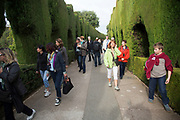 The Alhambra Palace and fortress complex located in Granada, Andalucia, Spain. Tourists walking through the topiary hedges on the south eastern side.