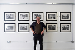 Craig Wallace editor of Sogo Arts magazine in the Sogo Arts gallery on Saltmarket in Glasgow, Scotland, UK. War photography exhibition by David Pratt current exhibition.
