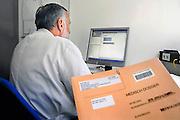 Nederland, Nijmegen, 22-5-2008een arts kijkt op zijn computer naar patientengegevens. Op de voorgrond een papieren patientendossier.Foto: Flip Franssen