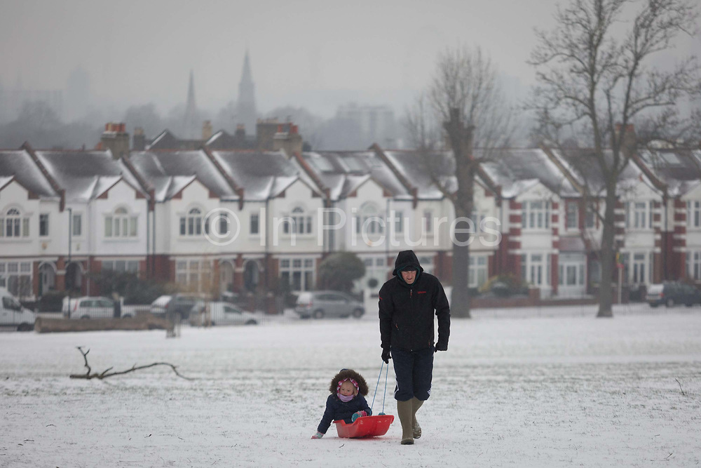 An adult pulls a child uphill on a small sledge in Ruskin Park, south London during the bad weather covering every part of the UK and known as the Beast from the East because Siberian winds and very low temperatures have blown across western Europe from Russia, on 1st March 2018, in Lambeth, London, England.