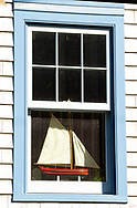 A blue window frame, with a red sailboat, inside the window with gray clapboard siding, in Castine, ME.