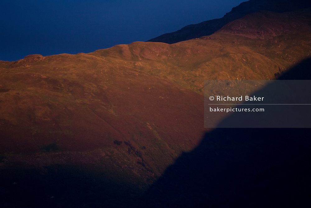 Late orange sunlight plays across upper slopes of Sgorr Dhearg, a mountain in Glencoe, Scotland.