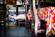 "A Chinese man takes a rest on a chair in his restaurant in PingYao, China, July 30, 2014. <br /> <br /> This image is part of the series ""24/7"", an ironic view on restless and fast-growing Chinese economy described through street vendors and workers sleeping during their commercial daily activity. <br /> <br /> © Giorgio Perottino"