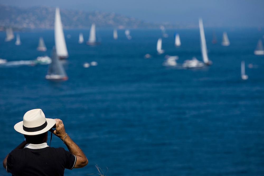 28SEP09 Les Voiles De St Tropez 2009..A spectator watches the racing through his binoculars from the top of the Citadel..