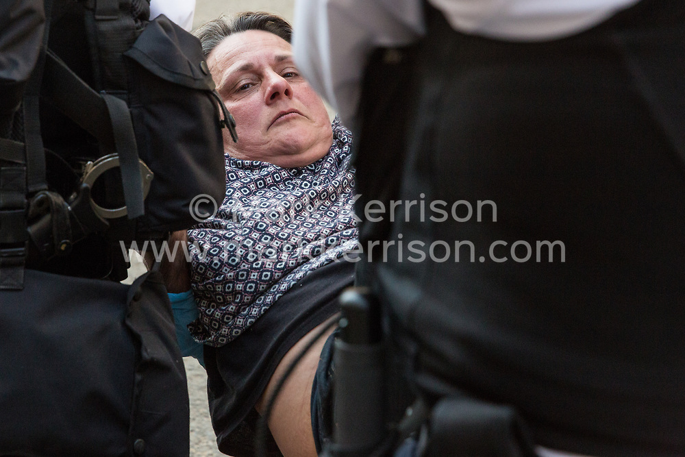 London, UK. 20th April 2019. Police officers arrest a climate change campaigner from Extinction Rebellion who had taken part in a lock-on at Oxford Circus following a policing operation to clear it of protesters earlier in the day. The heart of London's shopping district was blocked again for around two hours by the lock-ons on the sixth day of International Rebellion activities to call on the British government to take urgent action to combat climate change.