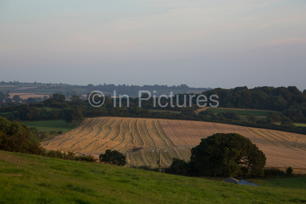 View over farmland at Kilburn in The Hambleton Hills on the edge of the North York Moors as a filed is harvested for it's crop on the day before rain is due. Yorkshire, England, UK. This is a farming area where rural living and the countryside is at the centre of life in this county.