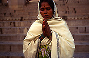 Radha, a low caste Hindu priestess, worships at the River Ganges in Varanasi, India
