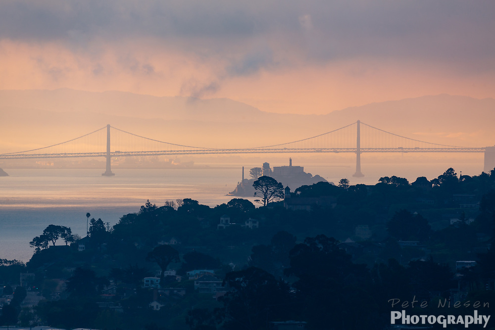 Pink sunrise scene of San Francisco Bay with Sausalito hills, Alcatraz, and the Bay Bridge