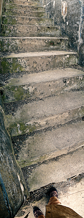 A pair of feet starts to climb concrete stairs at a gun battery at Fort Casey, Whidbey Island, Puget Sound, Washington, USA (vertical panorama)