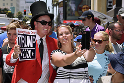 "July 25, 2018 - Los Angeles, CA, United States - A woman takes a picture with a Trump supporter holding a ""Keeping America Great! TRUMP 2020"" sign as workers replace the Hollywood Walk of Fame star of US President Donald Trump after it was destroyed by a man with a pickax in Los Angeles, California on July 25, 2018. (Credit Image: © Ronen Tivony/Pacific Press via ZUMA Wire)"