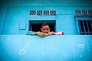 Un niño espera al inicio de la festividad del Corpus Christi, representada en Venezuela a traves del ritual magico-religioso de los Diablos Danzantes. Los Diablos de Naiguata se identifican por pintar sus propios trajes y decorarlos con cruces, rayas y circulos, figuras que impiden que el maligno los domine. Las mascaras son en su gran mayoria animales marinos. Llevan escapularios cruzados, crucifijos y cruces de palma bendita. Naiguata, 30 Mayo 2013. (ivan gonzalez)