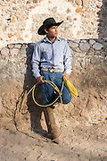A Mexican charro or cowboy poses in cowboy hat and lasso at a hacienda ranch in Alcocer, Mexico.