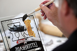 "© Licensed to London News Pictures. 17/08/2018. LONDON, UK. Sign writers practice applying gold leaf at ""Letterheads 2018: London Calling"", an international gathering of professional sign writers and lettering artists from over 30 countries.  The event is taking place at the Bargehouse, Oxo Tower Wharf in central London untikl 19 August.  Photo credit: Stephen Chung/LNP"