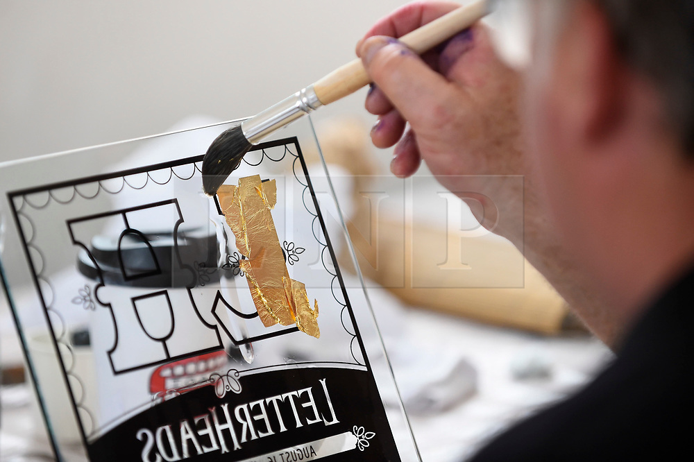 """© Licensed to London News Pictures. 17/08/2018. LONDON, UK. Sign writers practice applying gold leaf at """"Letterheads 2018: London Calling"""", an international gathering of professional sign writers and lettering artists from over 30 countries.  The event is taking place at the Bargehouse, Oxo Tower Wharf in central London untikl 19 August.  Photo credit: Stephen Chung/LNP"""