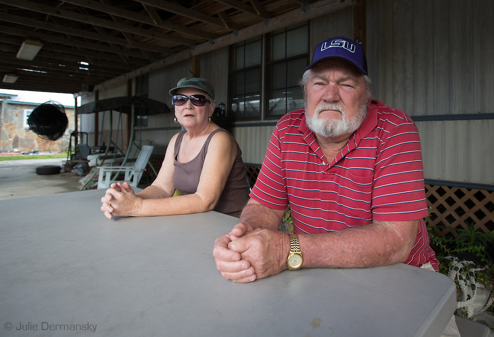 Henry and Carolyn Welsh in front of their home  near the Bayou Corn sinkhole have vacated their premises since Aug. 4th when the state declared a mandatory evacuation after the sinkhole opened up, only returning to pick up a check from Texas Brine to cover their relocation expenses. Carolyn is recovering from breast cancer and doesn't want to risk being around any extra potential carcinogens that may be in the air and water due to the sinkhole. The couple chose Bayou Corne  as their place to retire; now they want Texas Brine to buy them out so they can move elsewhere and get on with their lives.