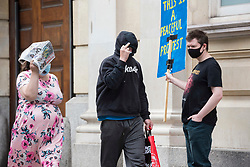 """© Licensed to London News Pictures; FILE PICTURE 22/06/2021; Bristol, UK. KANE ADAMSON (Nike top) walks past a man with a placard outside Bristol Crown Court. Kane Adamson is charged with riot and is one of the defendants facing charges related to a """"Kill the Bill"""" protest and riot against the Police, Crime, Sentencing and Courts Bill. During the protest on 21 March 2021 two police vehicles were burnt out and windows on Bridewell Police Station were smashed. The Police, Crime, Sentencing and Courts Bill proposes new restrictions on protests. Photo credit: LNP."""