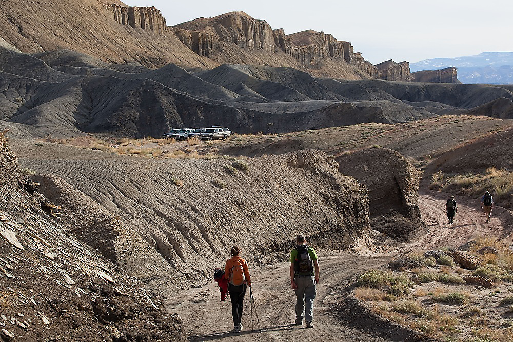 Students on a geology field trip with the University of Colorado hike on a road towards their vehicles parked at the foot of North Caineville Mesa, Utah.