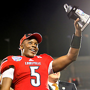 Louisville Cardinals quarterback Teddy Bridgewater (5) celebrates his MVP of the game award on the podium after the NCAA Football Russell Athletic Bowl football game between the Louisville Cardinals and the Miami Hurricanes, at the Florida Citrus Bowl on Saturday, December 28, 2013 in Orlando, Florida. Louisville won the game by a score of 36-9. (AP Photo/Alex Menendez)